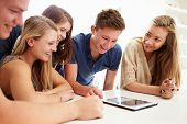 foto of 16 year old  - Group Of Teenagers Gathered Around Digital Tablet Together - JPG