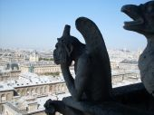 stock photo of notre dame  - Chimera of Notre Dame de Paris against the blue sky and a city panorama - JPG
