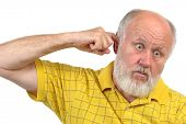 goofy bald senior man picking his ear with index finger