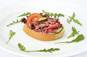 Sandwich with roast beef meat and vegetables on white dish