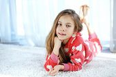 stock photo of pajamas  - Portrait of child in soft warm pajamas lying down on the carpet at home - JPG