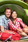 Couple camping in tent happy in romance smiling happy outdoors in forest enjoying love looking at vi