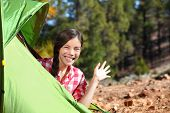 Camping woman waving hello from tent smiling happy outdoors in forest. Happy mixed race Asian Caucas