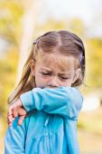 Child coughing or sneezing into arm