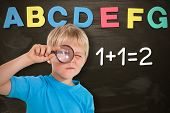 Cute boy looking through a magnifying glass against alphabet magnets stuck on blackboard up to letter g