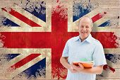 Mature student holding notebooks against union jack flag in grunge effect