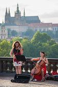 Street musicians perform with Prague Castel on background