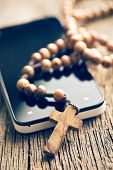 rosary and smartphone on old table