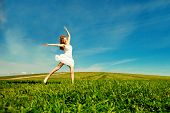 Woman jumping. Young beautiful girl jumping in a field on the grass under a blue sky in the clouds.