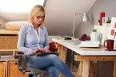 Young blonde woman sitting at home, using tablet computer.
