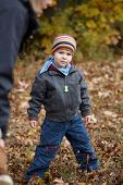 Portrait of serious casual little kid standing at outdoor park wearing warm clothes. Looking at camera,