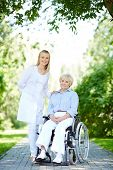 Pretty nurse taking care of senior patient while taking walk in park