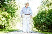 Portrait of happy senior patient walking in the park in summer