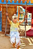 Child swinging on a swing in playground.