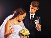 Wedding couple kissing and drinking champagne.Black background.