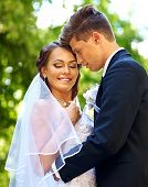Groom kissing bride outdoor.