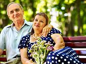 Old woman sit in hand of senior man. Outdoor.