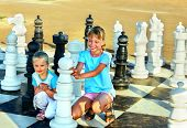 Children playing big chess outdoor.