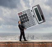 Young businessman carrying huge calculator in hands