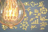Close up of vintage glowing light bulb with business graph