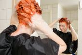 stock photo of hair dye  - Caucasian woman with short hair dying her hair red in front of mirror in her own bathroom - JPG
