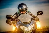 Biker in helmet and leather jacket racing on the road with the sun in the background
