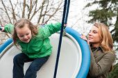 Mother Pushing Her Daughter On A Flying Sauser Swing
