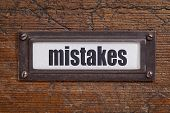 mistake  - file cabinet label, bronze holder against grunge and scratched wood