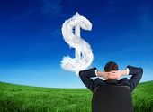 Composite image of businessman sitting in swivel chair against cloud dollar