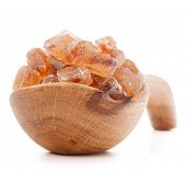 Brown cane caramelized lump sugar in wooden bowl isolated on white background cutout