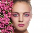 Close-up horizontal portrait of young beautiful girl with fresh make-up and pink roses over white background, copy space