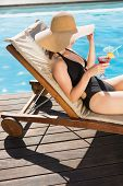 Side view of beautiful young woman holding drink by swimming pool