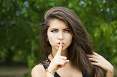 Young beautiful brunette woman has put forefinger to lips as sign of silence, against green summer g