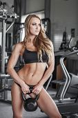 Woman Posing With Kettlebell In Gym