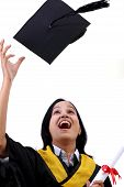 Happy Young Female Graduate Tossing Up Her Hat