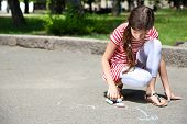 Cute girl drawing with chalk on asphalt