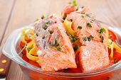fresh fried natural pink salmon on italian traditional tagliatelle backed with tomato and vegetables