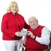 A senior woman happily delivering a gift to her husband.  On a white background.