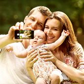 Family With Baby In Park  Taking Selfie By Mobile Phone