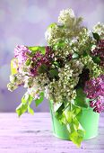 Beautiful lilac flowers in vase, on color wooden table, on light background