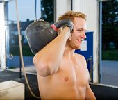 Smiling young man exercising with kettlebell in Cross Fitness gym