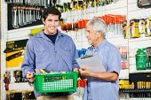Senior man looking at son carrying basket full of tools in hardware store