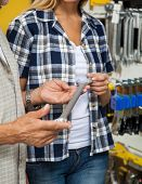 Midsection of woman with father holding wrench while standing in hardware shop