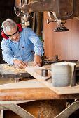 Senior carpenter using bandsaw to cut wood in workshop