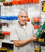 Portrait of happy senior customer holding packed product in hardware shop