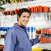 Portrait of confident male customer selecting screwdrivers in hardware shop