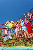 Many kids standing on the ropes of playground net