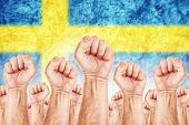 stock photo of labourer  - Sweden Labour movement workers union strike concept with male fists raised in the air fighting for their rights Swedish national flag in out of focus background - JPG
