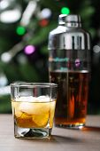 Glass With Whiskey And Ice On Wooden Table