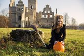 picture of pale skin  - Witch with pale skin with pumpkin is smiling - JPG